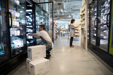 Male worker restocking refrigerated case in grocery store