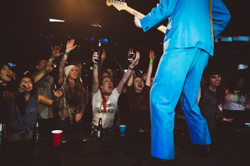Crowd cheering for rockabilly musician performing on stage at music concert in nightclub