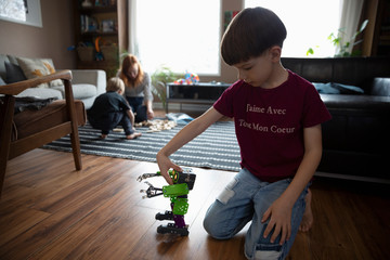 Boy playing with robot toy on living room floor