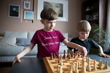 Brothers playing chess in living room