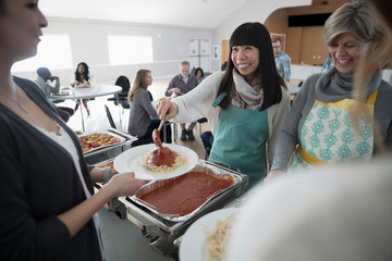 Smiling woman serving spaghetti at soup kitchen community dinner