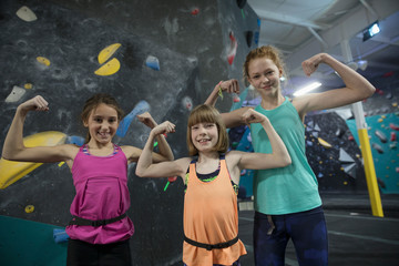 Portrait smiling, confident, strong, tough girl rock climbers flexing muscles at climbing wall in climbing gym