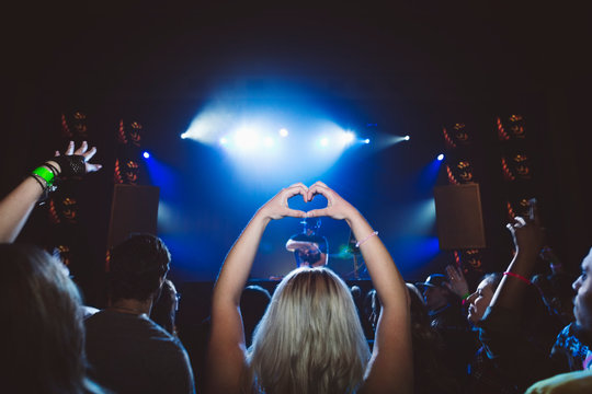 Young woman forming heart-shape with hands at music concert in nightclub