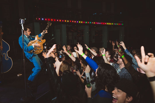 Enthusiastic millennial crowd cheering for rockabilly guitar musician at music concert in nightclub