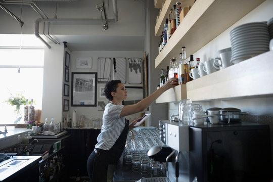 Female bartender organizing alcohol bottles in bar