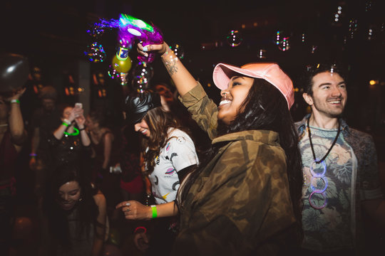 Playful, exuberant young female millennial with bubble maker dancing in nightclub