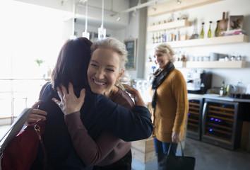 Happy senior women friends greeting, hugging in cafe
