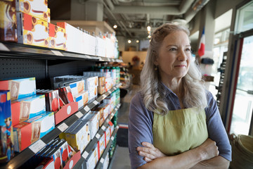 Portrait confident female senior worker in grocery store aisle