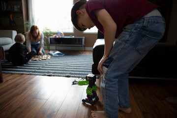 Boy playing with toys on living room floor