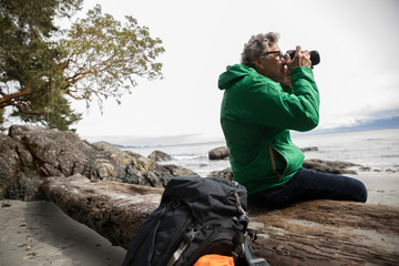 Active senior male backpacker using camera on rugged beach