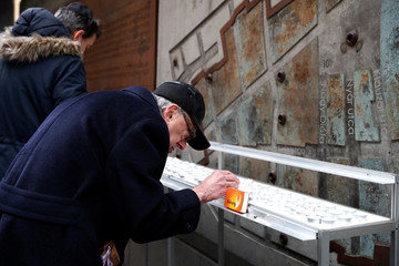 Man lights candle front of the Memorial Ghetto Wall during the commemoration of the liberation of the Budapest ghetto by the Red Army, 75 years ago in Budapest