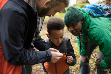 Trail guide showing branch to curious boy and father in woods