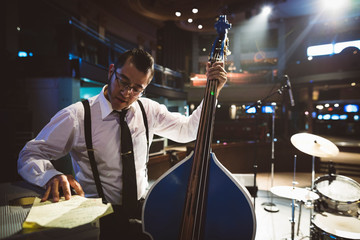 Musician with double bass preparing, reviewing stage set
