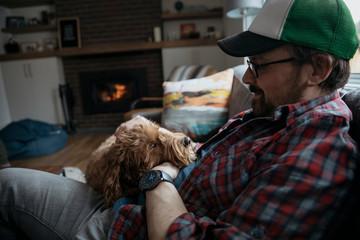 Man petting cute dog on living room sofa