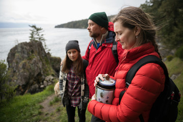 Family with urn spreading ashes on cliff overlooking ocean