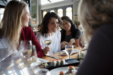 Women friends drinking wine and eating sushi at restaurant