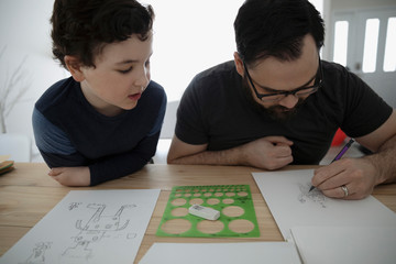 Curious son watching father drawing robot on paper