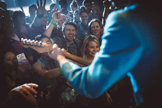 Crowd cheering for rockabilly musician playing electric guitar on stage at music concert