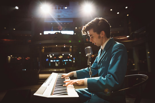Rockabilly musician playing electric piano on stage