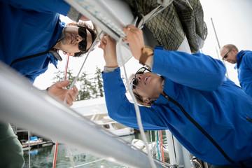 Sailing team preparing sail on sailboat