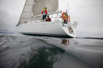 Sailing team training on sailboat on ocean