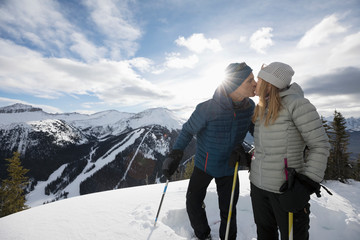 Affectionate active senior couple skiers kissing on sunny mountain