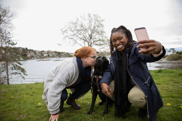 Women friends with seeing eye dog taking selfie at lakeside