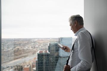 Senior businessman using smart phone at urban office window