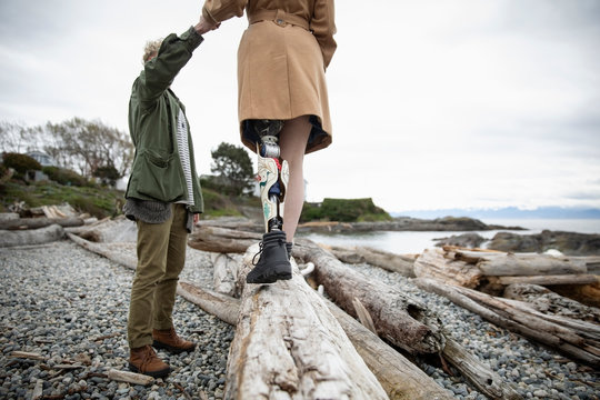 Young man holding hands with amputee girlfriend walking on beach driftwood
