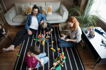 Family playing with building block toys on living room floor