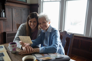 Affectionate senior mother and daughter looking at photo albums