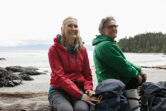 Carefree active senior couple backpacking, resting on rugged beach