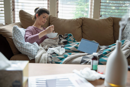 Sick woman working at home, eating soup on sofa