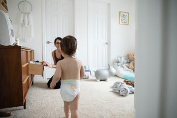 Mother watching baby son in diaper walking in nursery