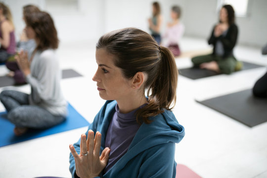 Serene woman practicing yoga with hands at heart center