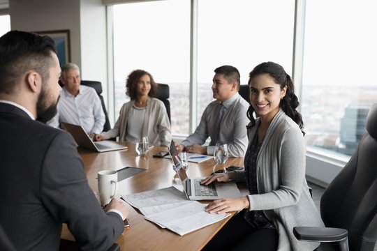 Portrait smiling, confident businesswoman at laptop in conference room meeting