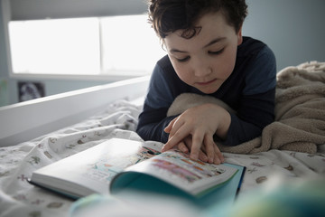 Curious boy reading book on bed