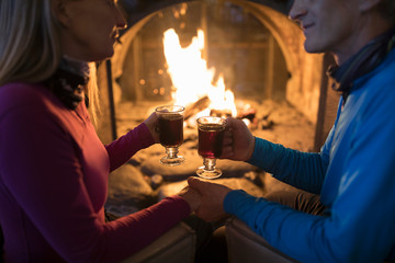 Affectionate active senior couple enjoying hot toddy apres-ski at fireplace