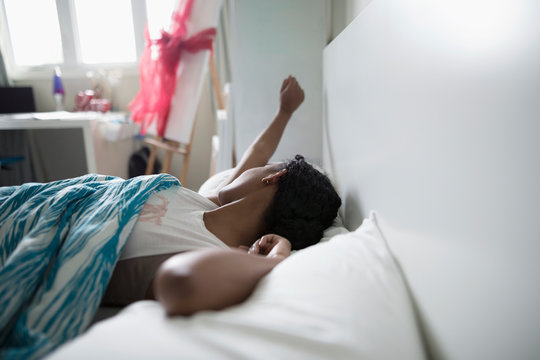 Teenage girl waking, stretching in bed