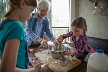 Grandmother and granddaughters baking in kitchen