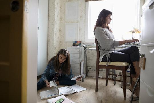 Tween daughter studying on floor behind mother working in home office