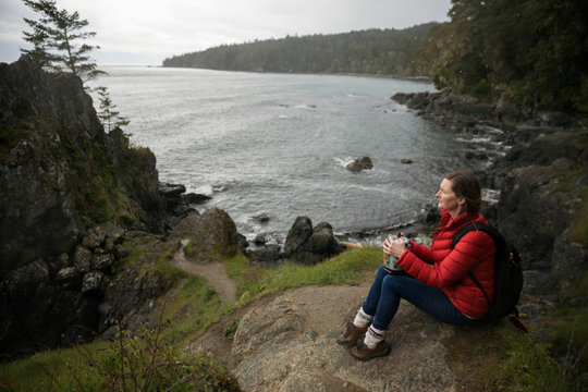 Woman with urn spreading ashes on cliff overlooking ocean
