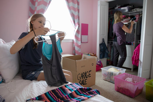 Mother and daughter organizing bedroom closet, donating clothes