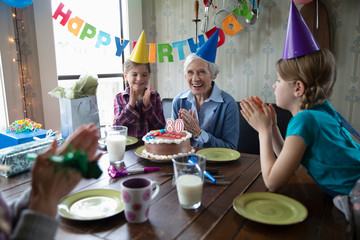 Happy granddaughters and grandmother celebrating birthday with cake