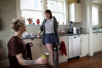 Young woman amputee drinking coffee, talking with boyfriend in kitchen