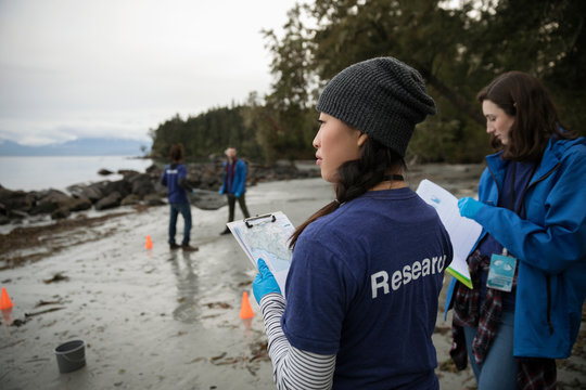 Eco-friendly female scientist with clipboard on beach