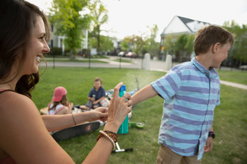Mother spraying sunscreen on son in park