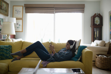 Tween girl relaxing, listening to music with mp3 player and headphones on sofa