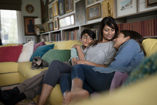 Affectionate mother and tween daughter and son cuddling on sofa