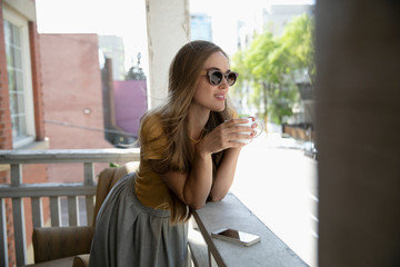 Young woman drinking coffee on urban apartment balcony